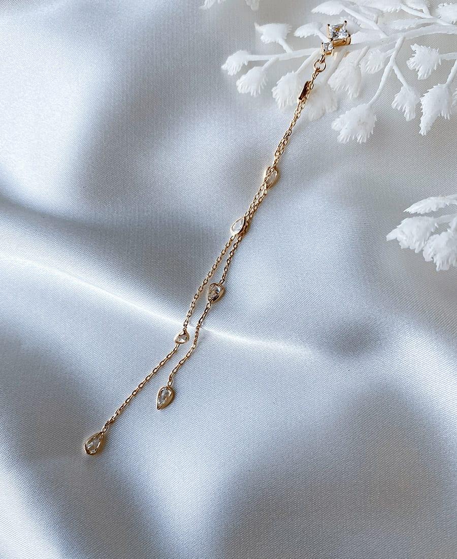 זוג עגילים עשויים משילוב של זרקונים, שרשרת ואלמנטים בציפוי זהב.