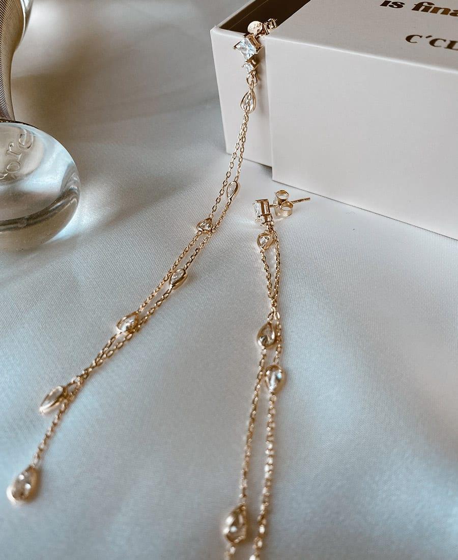 זוג עגילים עשויים משילוב של זרקונים, שרשרת ואלמנטים בציפוי זהב 14 קראט.