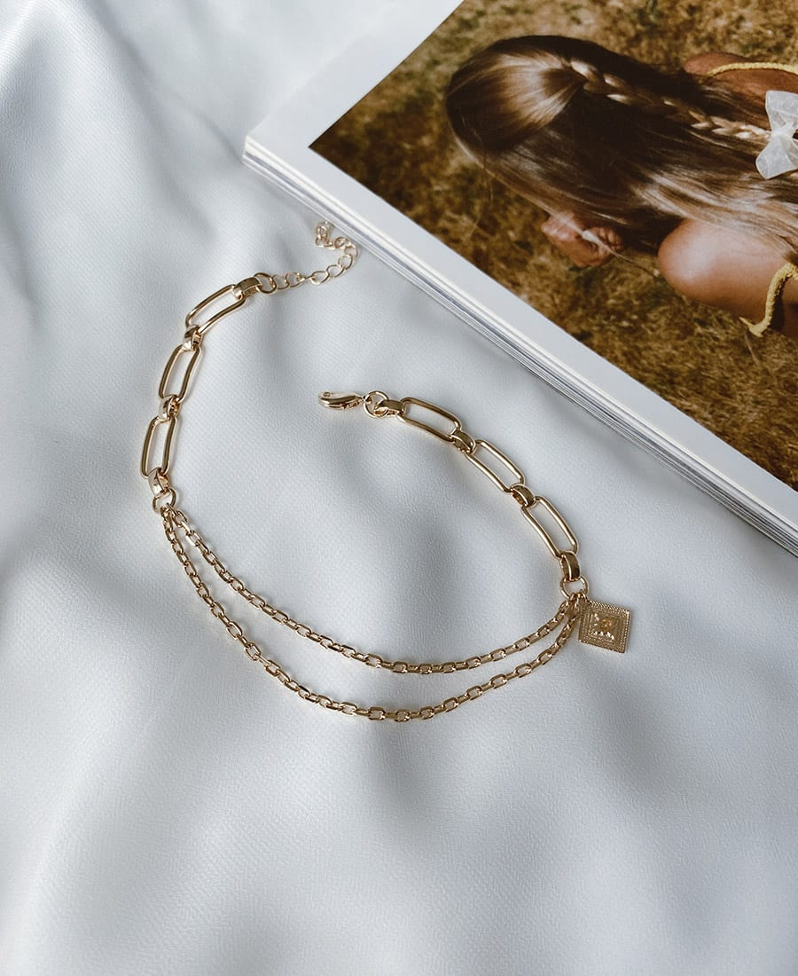 צמיד רגל פאולין עשוי משרשראות מצופות זהב.